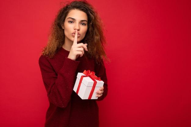 Mujer aislada sobre fondo rojo pared vistiendo un suéter rojo sosteniendo una caja de regalo mirando a la cámara y mostrando el gesto de shh y el significado de estar en silencio. copia espacio