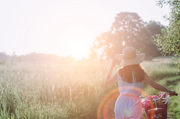 Mujer al aire libre con bicicleta vintage y una cesta de flores y disfrutando del atardecer contra