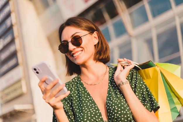 Mujer al atardecer con coloridas bolsas de compras y estacionamiento por centro comercial feliz con teléfono móvil