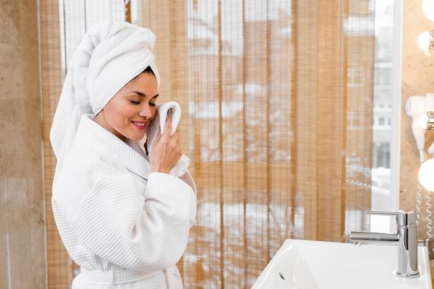 Mujer con albornoz en habitación de hotel