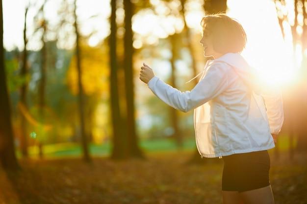 Mujer alegre activa corriendo en el parque local