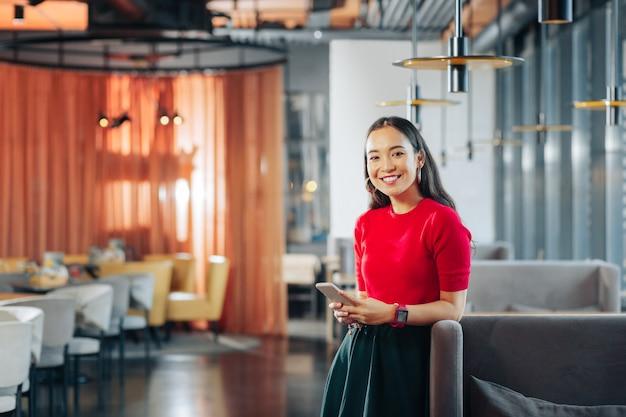 Mujer alegre alegre mujer de moda darkeyed de pie en un gran restaurante espacioso