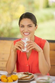 Mujer alegre. alegre mujer de ojos oscuros sonriendo mientras come sándwich y bebe leche