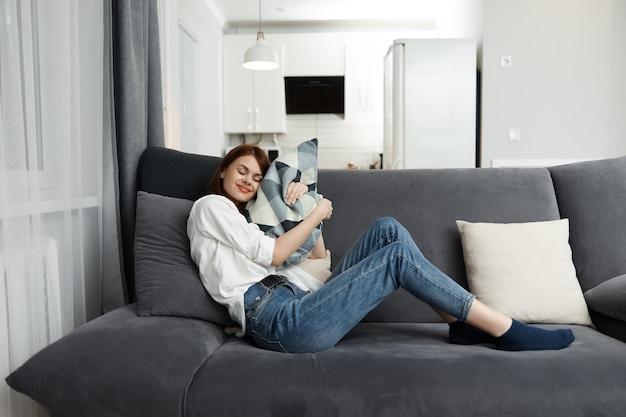 Mujer alegre con una almohada en sus manos en un sofá en el interior de un apartamento