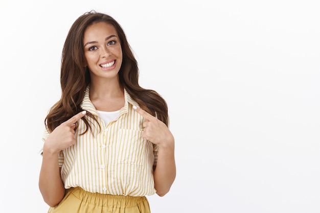 Mujer alegre y ambiciosa terminar la universidad, decidida a conseguir un puesto de trabajo prometedor, señalando a sí misma, tocando el pecho con los dedos y sonriendo linda, ofreciendo ayuda, convencida de que puede lidiar con el problema