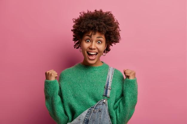 Mujer alegre y animada con cabello afro hace un puño y celebra la victoria