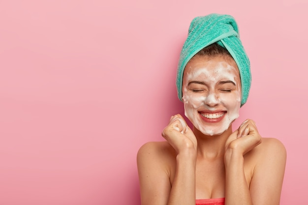 Mujer alegre aprieta los puños, sonríe ampliamente, muestra los dientes blancos, se lava la cara con jabón, elimina la suciedad, disfruta de tratamientos higiénicos en casa, envuelta en una toalla suave