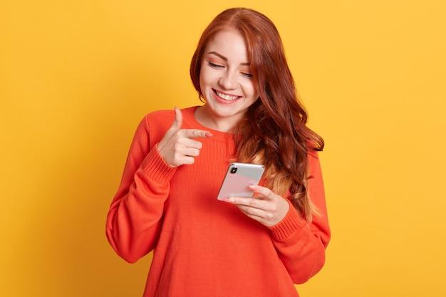 Mujer alegre apuntando a la pantalla de su teléfono inteligente con el dedo índice, mirando el teléfono móvil con una sonrisa encantadora