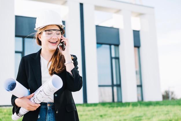 Mujer alegre arquitecto hablando por teléfono
