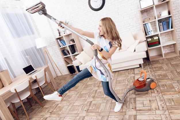 Mujer alegre con aspiradora en el apartamento.