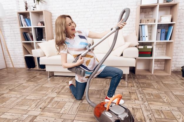 Mujer alegre con aspiradora sala de limpieza.
