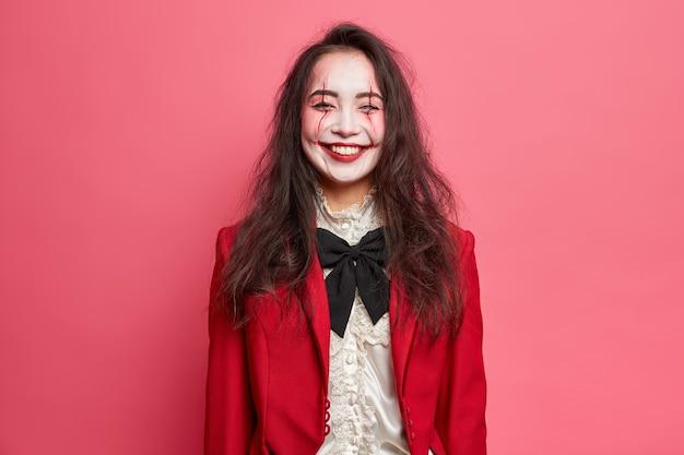 La mujer alegre y aterradora con maquillaje de halloween tiene la cara pálida y usa un disfraz para poses de fiesta de carnaval contra la diversión de la pared rosa en vacaciones