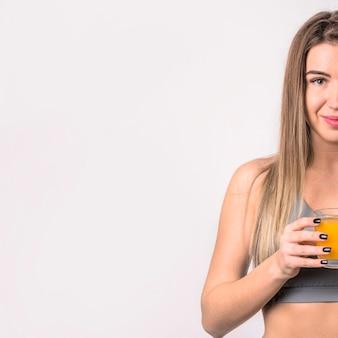 Mujer alegre atractiva con vaso de jugo