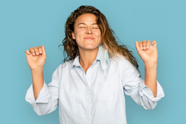 Mujer alegre bailando sobre fondo azul.