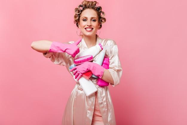 Mujer alegre en bata de seda muestra los pulgares hacia arriba y tiene detergente