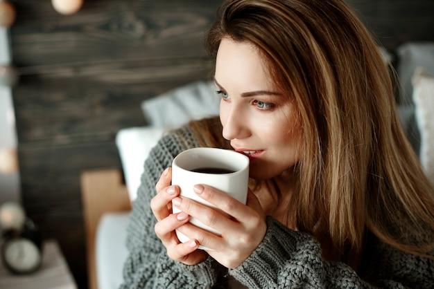 Mujer alegre bebiendo café por la mañana