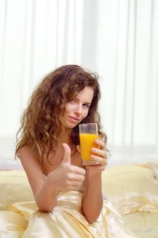 Mujer alegre bebiendo un jugo de naranja sentada en su cama en casa