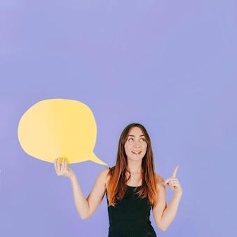 Mujer alegre con bocadillo de diálogo apuntando hacia arriba