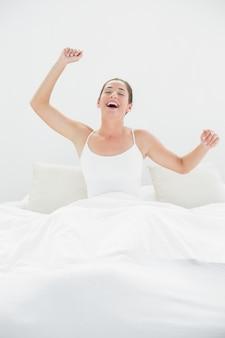 Mujer alegre bostezando mientras estira los brazos en la cama