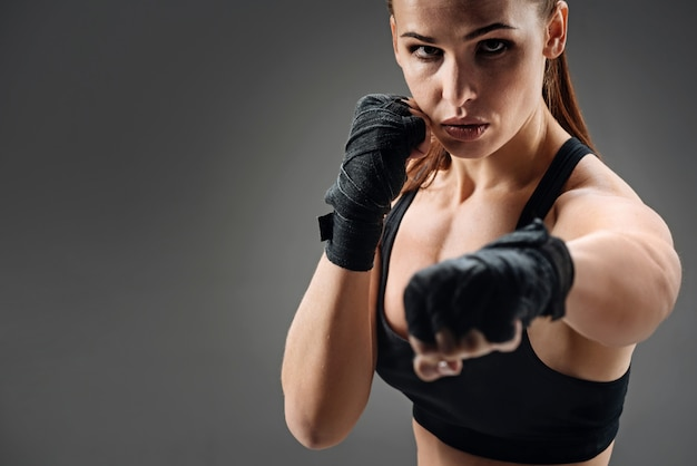 Mujer alegre boxeo en un gris