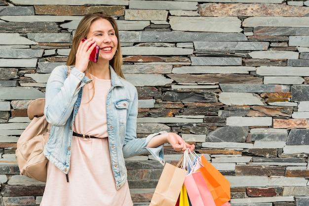 Mujer alegre con brillantes bolsas de compras hablando por teléfono