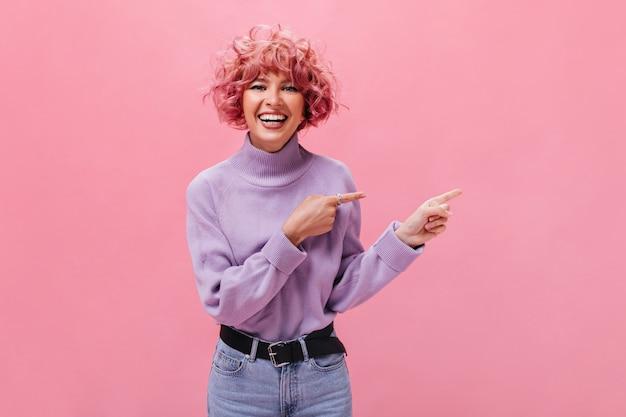 Mujer alegre y de buen humor en suéter morado sonriendo y apuntando al lugar para el texto aislado