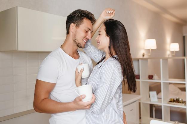 Mujer alegre con cabello brillante sonriendo al novio, disfrutando del café de la mañana
