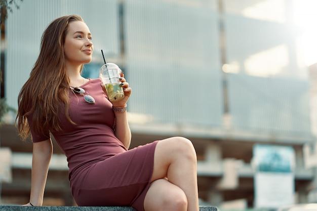 Mujer alegre en la calle bebiendo mañana refrescante bebida