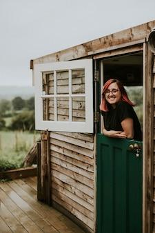 Mujer alegre en una casa de madera