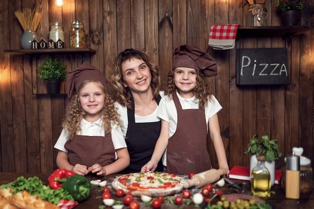 Mujer alegre con chicas lindas en delantales y sombreros sonriendo y mirando a la cámara durante la preparación de pizza en la cocina en casa