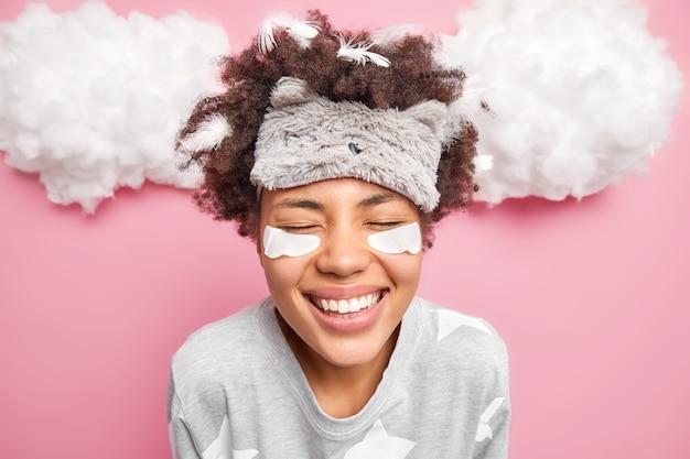 Una mujer alegre cierra los ojos, sonríe ampliamente, tiene dientes blancos, usa un pijama con los ojos vendados, tiene plumas pegadas al cabello rizado después de dormir, tiene parches de colágeno debajo de los ojos