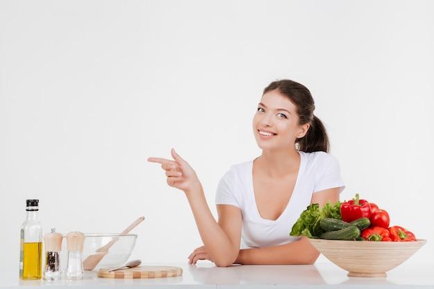Mujer alegre cocinar con verduras mientras apunta a la izquierda