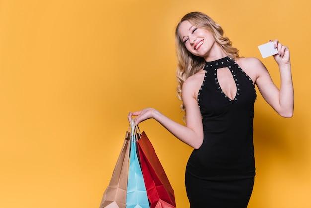 Mujer alegre de compras con bolsas y tarjeta