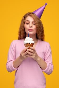 Mujer alegre con cupcake de cumpleaños