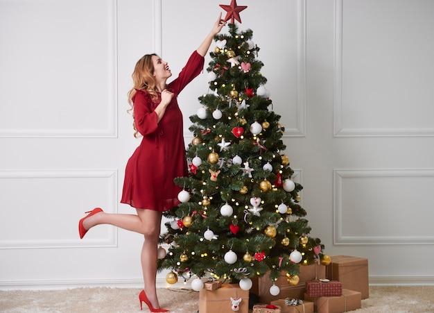 Mujer alegre decorar el árbol de navidad