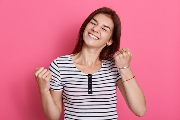 Mujer alegre emocionada con expresión alegre, vítores y puños apretados, celebrando su éxito, posa contra la pared rosa, viste una camiseta informal a rayas blancas y negras.