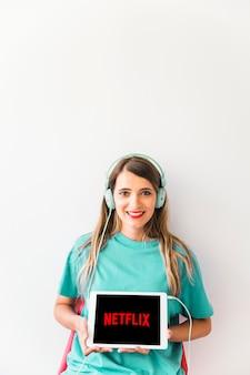 Mujer alegre en auriculares mostrando el logo de netflix