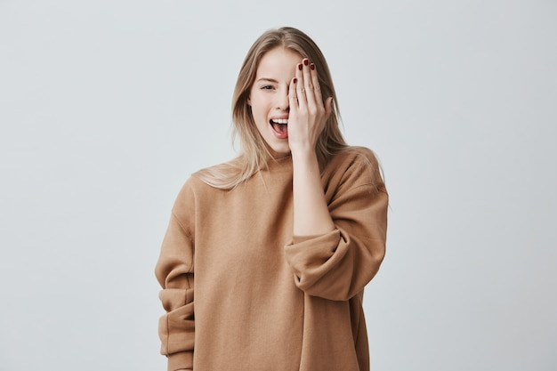 Mujer alegre encantadora en suéter suelto con cabello rubio sonriendo felizmente, divirtiéndose en el interior, cerrando un ojo con la mano.