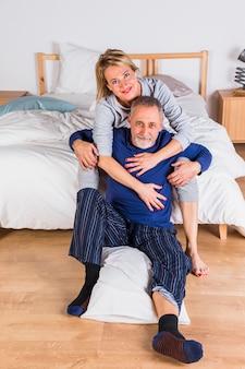 Mujer alegre envejecida que abraza al hombre con la almohada cerca de cama