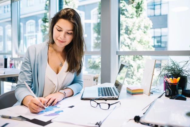 Mujer alegre escribiendo en documentos
