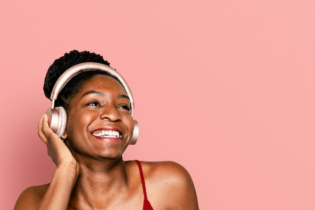 Mujer alegre escuchando música a través de auriculares dispositivo digital