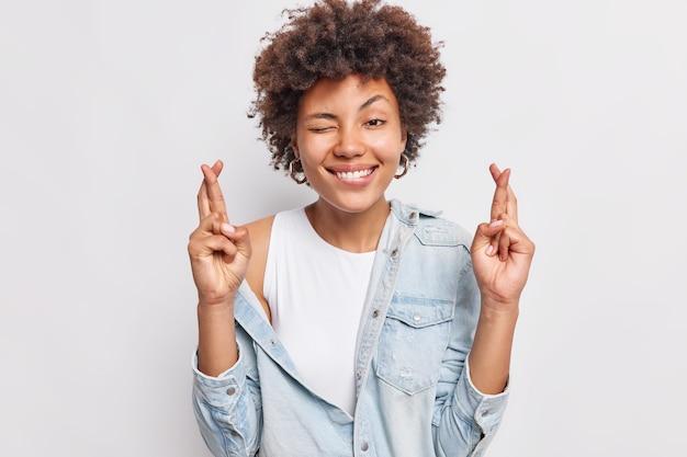 La mujer alegre y esperanzada sonríe ampliamente, mantiene los dedos cruzados, anticipa resultados positivos, usa una camisa de mezclilla, ora por la buena suerte, se opone a la pared blanca