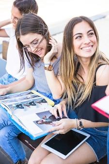 Mujer alegre estudiando con amigos y mirando lejos