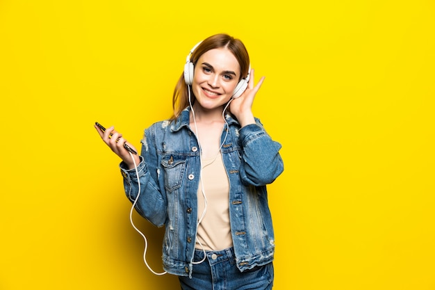 Mujer alegre feliz con auriculares escuchando música desde el estudio de teléfono inteligente disparo aislado en la pared amarilla