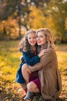 Mujer alegre feliz divirtiéndose con su niña en color de otoño