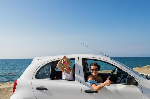 Mujer alegre feliz con la hija que se coloca en coche con los brazos extendidos y que mira la cámara. relajarse en un auto. viaje en coche las mujeres jóvenes felices y el niño disfrutan de la libertad en vacaciones de viaje.
