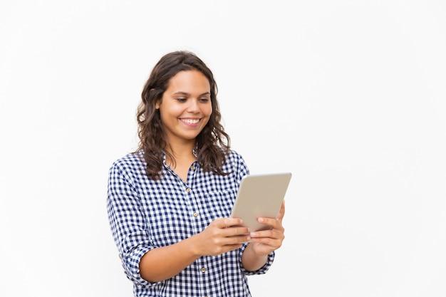 Mujer alegre feliz que usa la tableta