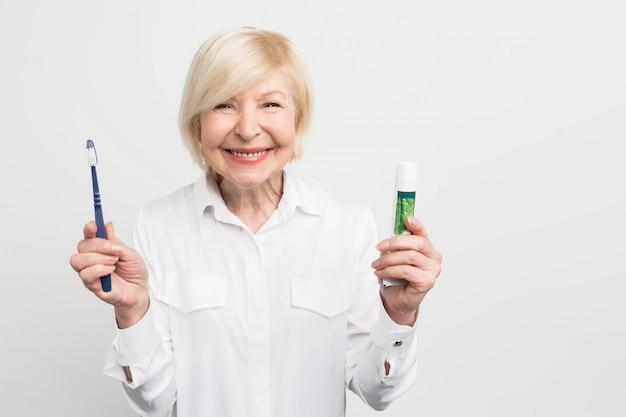 Mujer alegre y feliz está sosteniendo una pasta de dientes y un cepillo de dientes. ella está mostrando su hermosa sonrisa.
