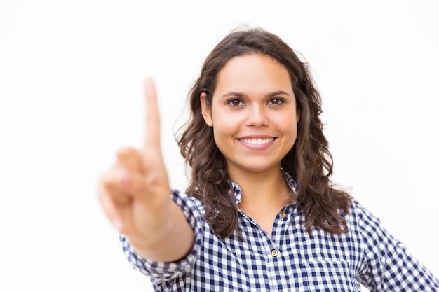 Mujer alegre feliz tocando el tablero de cristal