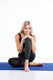 Mujer alegre fitness sentado y posando